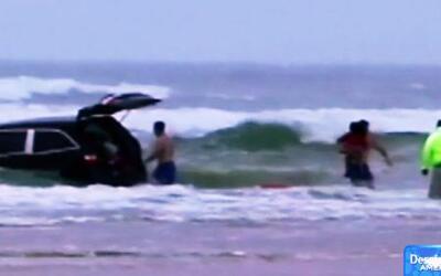 Madre conduce su coche mar adentro con sus tres hijos dentro