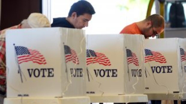 Tres electores votan en una mesa electoral instalada en un subirbio de A...