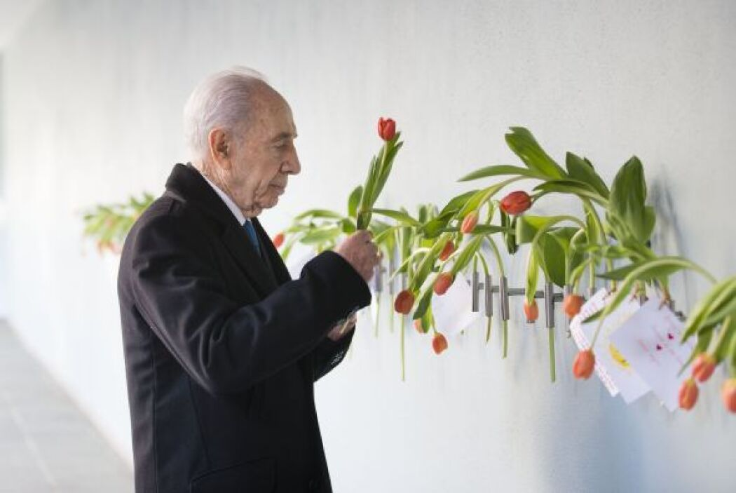 El presidente israelí, Shimon Peres coloca un tulipán en la pared en su...
