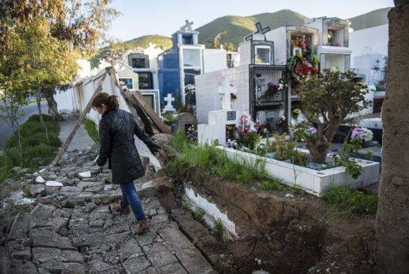Una mujer camina entre los destrozos provocados en un cementerio por el...