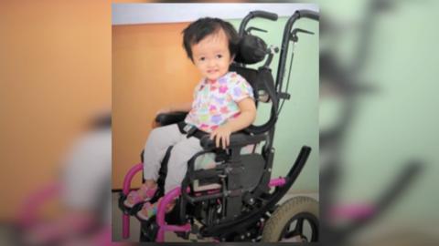 Niña beneficiada con silla de ruedas gratis.