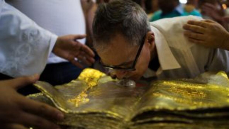 Un hombre besa la pequeña urna que guarda gotas de sangre del Papa Juan...