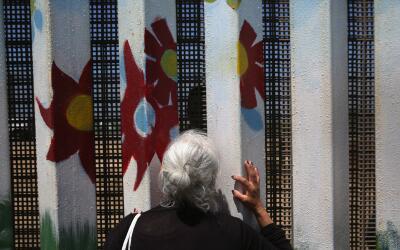 Una mujer toca el muro fronterizo entre Estados Unidos y México