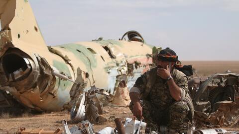 Un soldado de las Fuerzas Democráticas Sirias descansa junto a un...