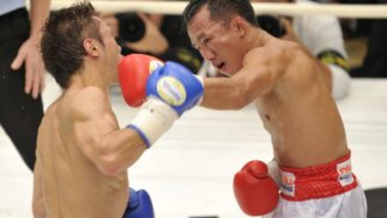 Akira Yaegashi (izquierda) intercambia golpes con Pornsawan Porpramook c...