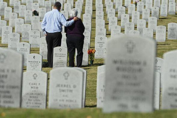 Luis Calderón y su madre Lydia Calderón observan la tumba de su padre y...