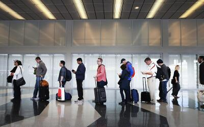 Viajeros hacen fila para ingresar a EEUU en el Aeropuerto Internacional...