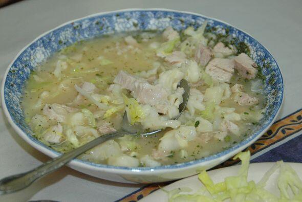 Pozole blanco con carne de cerdo, maíz, cebollita y orégano.