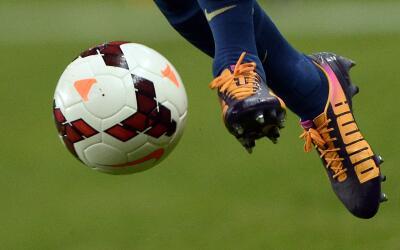 Deportista le pega al balón de fútbol