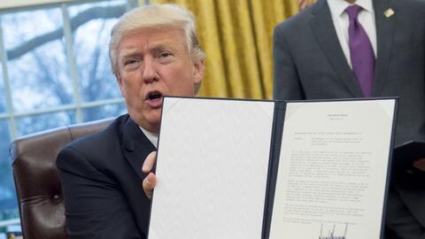 El presidente Trump sostiene en sus manos la orden ejecutiva firmada que...