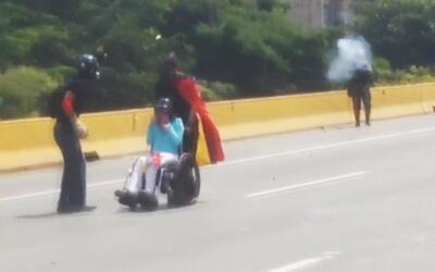 Guardia Nacional venezolana dispara gas lacrimógeno a un manifestante en...