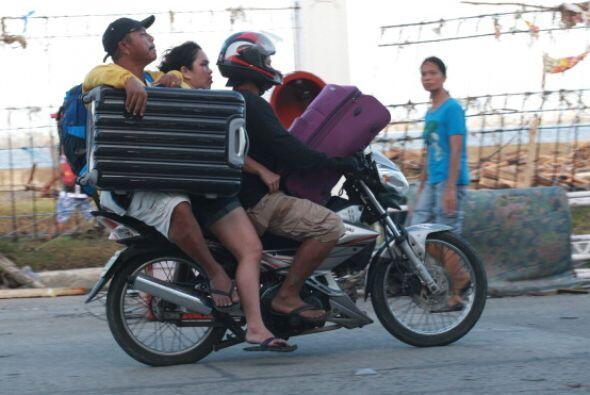 En Filipinas la gente trata de salvar las pertenencias que les dejó el t...