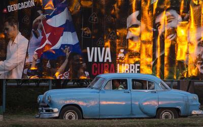 Un taxista en un automóvil estadounidense clásico recorre una calle de L...