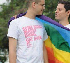 Felipe y su esposo, con una bandera de arco iris. Foto Cortesía.