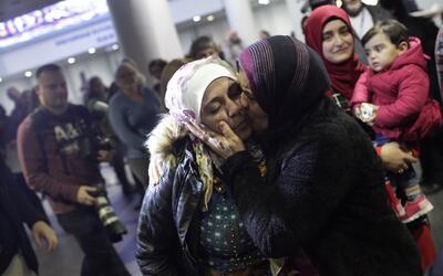 La refugiada siria Baraa Haj Khalaf recibe un beso de su madre Fattoum H...