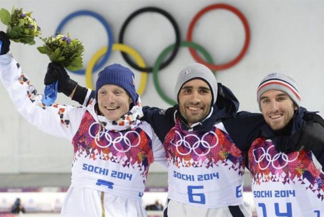 El esquiador francés Martin Fourcade (al centro) celebra en el podio la...
