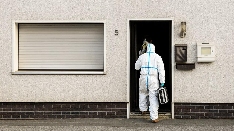 Un policía entra en la casa donde han sido encontrados los restos de los...