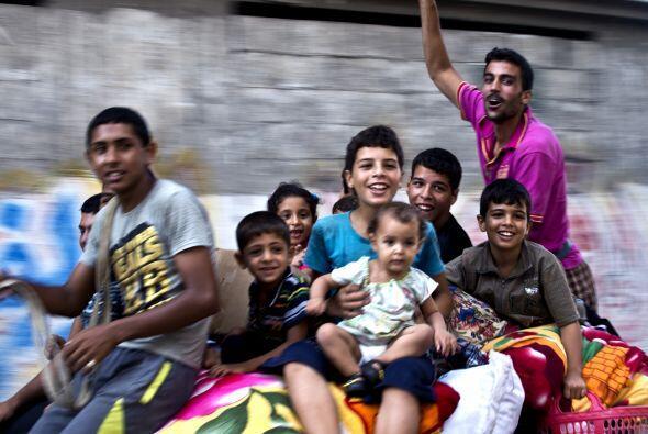 Tras el fin de la guerra, jovenes y niños pasean en un carruaje j...