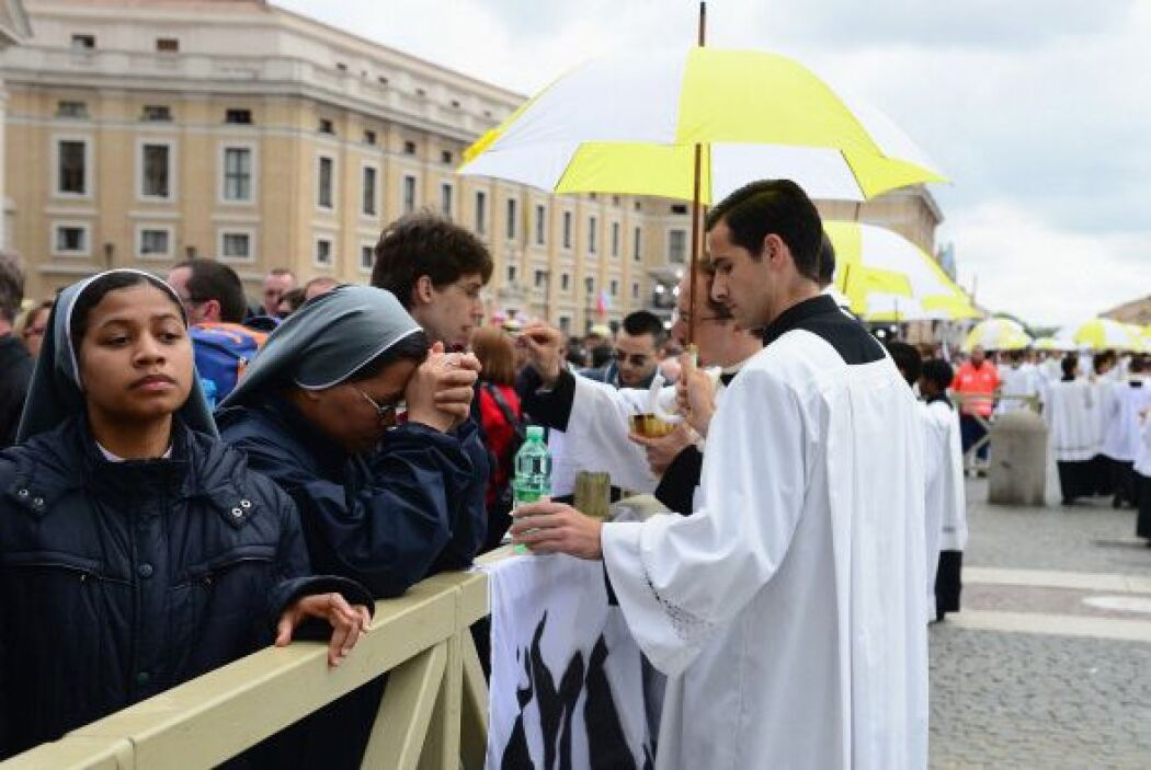 Los sacerdotes dan la comunión a los feligreses que estaban en posibilid...