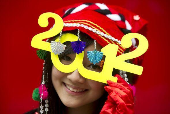 Una modelo porta feliz unos lentes con diseño de los números 2012 en un...
