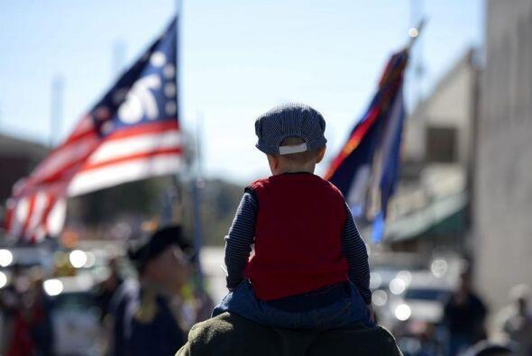 Un niño, subido sobre los hombros de su padre, observa el desfile...