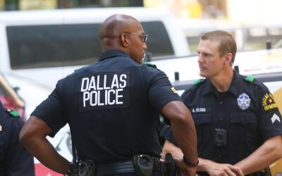 Dos policías protegen una vigilia en honor a los oficiales que murieron...