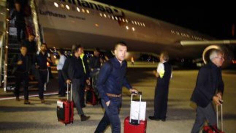 Podolski camina tras bajar del avión, mientras que Khedira y el técnico...