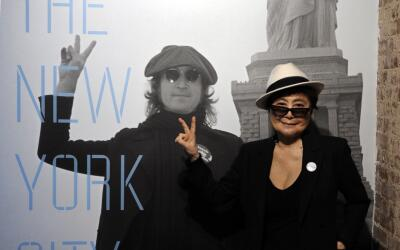 Yoko Ono, the widow of John Lennon, stands next to a photo of him as she...