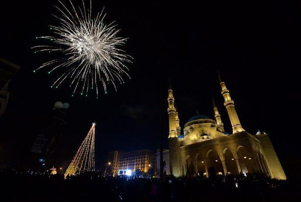 Fuegos artificiales iluminan sobre un árbol de Navidad gigante durante l...