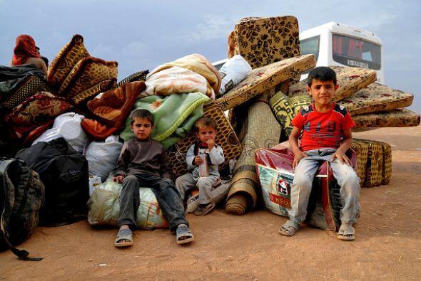 Estos niños descansan sentados sobre sus pertenencias luego de un largo...