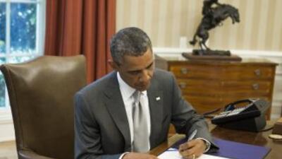 Momento en que el presidente firmó la ley aprobada previamente por el Co...