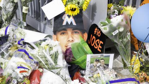 Flowers, photos, candles and baseballs make up an improvised shrine to M...