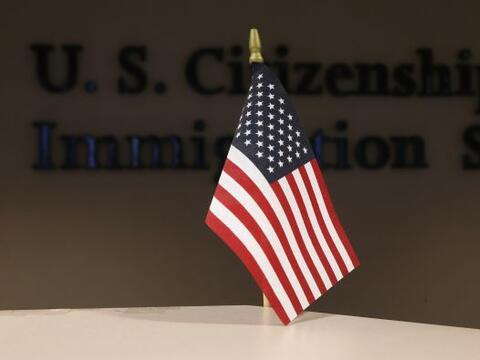 Una bandera de EEUU da la bienvenida a 154 inmigrantes durante una cerem...