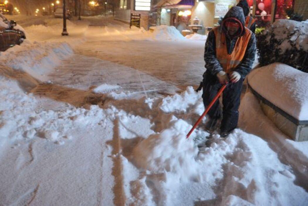 Un trabajador limpia la nieve acumulada en la calle Chevy Chase en Maryl...