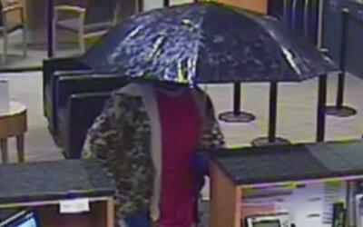 Buscan a sospechoso que robó un banco bajo un paraguas en Carrollton