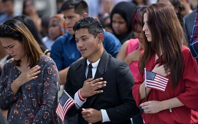 People sing the national anthem during a naturalization ceremony at the...