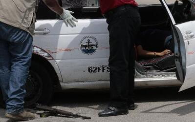 Agentes de policía inspeccionan el vehículo en que viajaban los presunto...