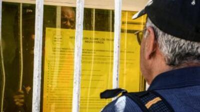 Un cubano leyendo la información sobre la nueva política migratoria cubana.