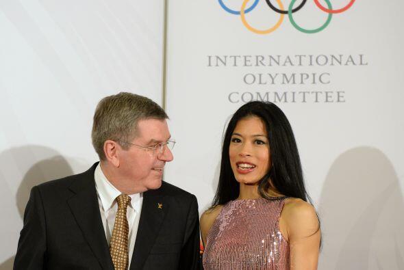 Thomas Bach, el presidente del Comité Olímpico Internacional le sonríe a...