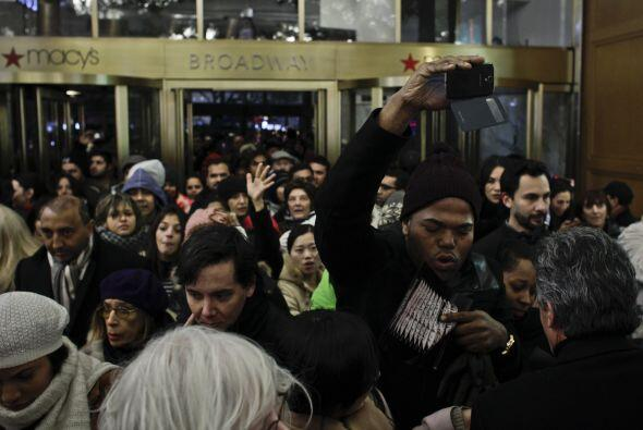 Mientras tanto, cientos de personas entran a la tienda Macy's de Herald...