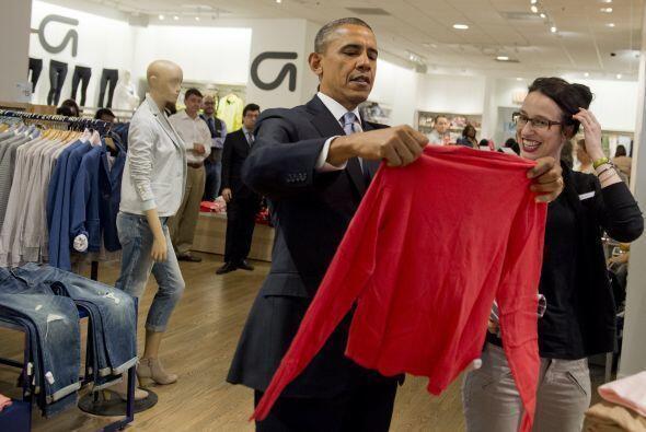 El presidente Barack Obama sostiene una camisa mientras hace sus compras...