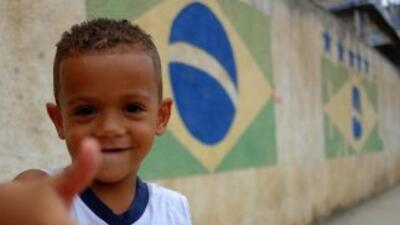 Un niño hace una señal positiva en una calle de la favela Ciudad de Dios...