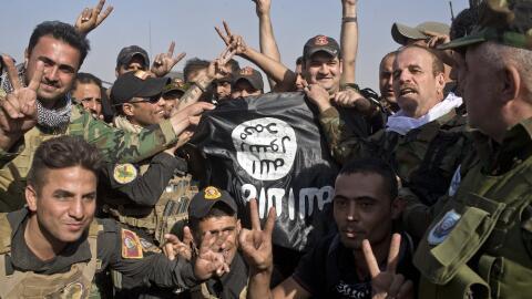 Fuerzas iraquíes y curdas sostienen una bandera de ISIS encontrad...