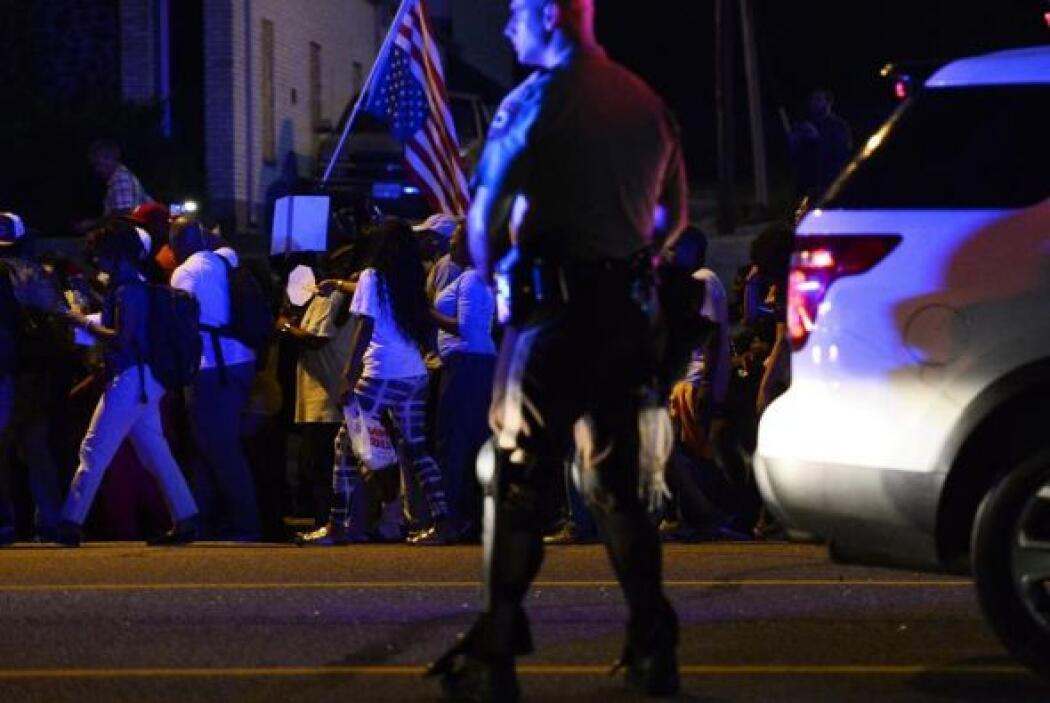 Un policía vigila a manifestantes durante otro día de protestas por la m...