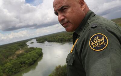 U.S. Border Patrol agent Jose Perales looks into Mexico from the U.S.-Me...