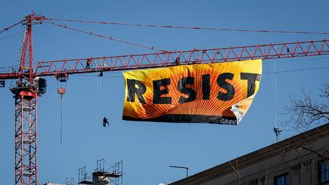 """Activists from Greenpeace hung a 70 ft. banner inscribed with the word """"..."""