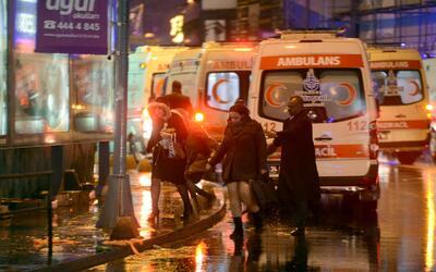 Gente huye del club nocturno en una calle repleta de ambulancias.