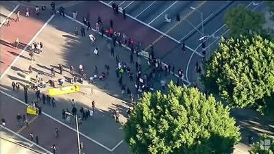 Grupo de inmigrantes que bloquean la calle cerca del edificio de ICE en...