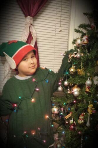 Eric García de 7 años disfrazado de duende mientras decora su arbolito.