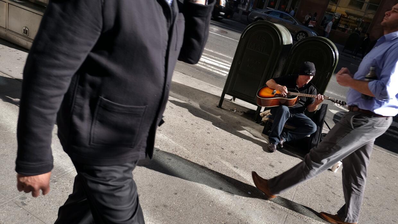 Un desempleado toca guitarra en NY en espera de propinas